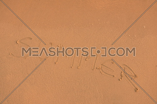 The Word Summer Written in the orange Sand background on a Beach at sunset