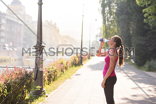 Athlete woman drinking water from a bottle after jogging in the city on a sunny day