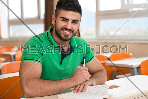 Portrait Of Young Arabic Male College Student With Book Sitting In Classroom Alone
