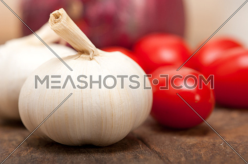 onion garlic and tomatoes foundations of Italian food on rustic table
