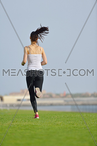 Running in city park. Woman runner outside jogging at morning with Dubai urban scene in background
