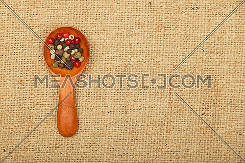 Mix of peppercorn in wooden scoop on brown burlap jute canvas background