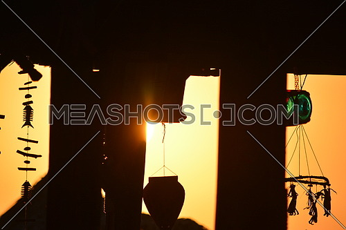 mid shot for dream catchers and accessories hanged to a wall in silhouette at sunset.