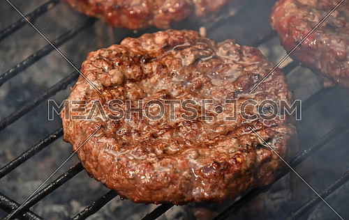 Beef or pork meat barbecue well done burgers for hamburger prepared grilled on bbq smoke grill, close up
