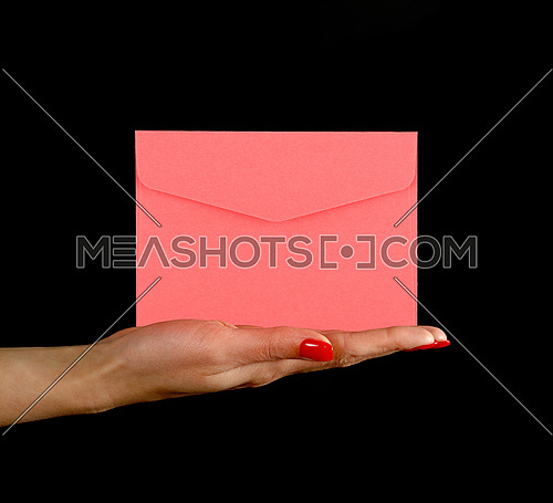 Woman hand palm with red nails holding and presenting pink paper envelope over black background, side view