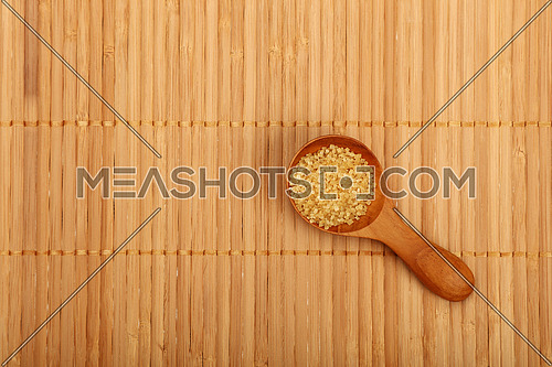 Wooden round scoop spoon of brown cane sugar on bamboo mat background, top view