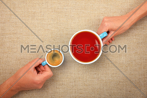 Different habits, two hands, man and woman, holding full cups, small espresso coffee and big black tea, together over linen canvas background