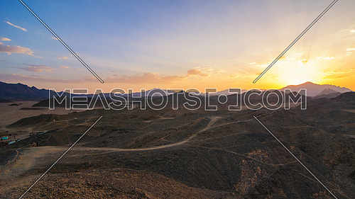 Wonderful landscape,Arabian desert of stone, Egypt with mountains at sunset.To the left of the desert nomad huts,