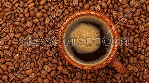 Close up one wooden cup full of Turkish black coffee over background of coffee beans with slow motion animated cinemagraph spin of coffee froth