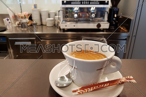 Good morning hot cup of coffee at the barin front of a blurred espresso machine bacground