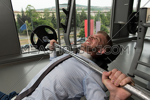 Business Man In Gym Exercising Chest On The Bench Press