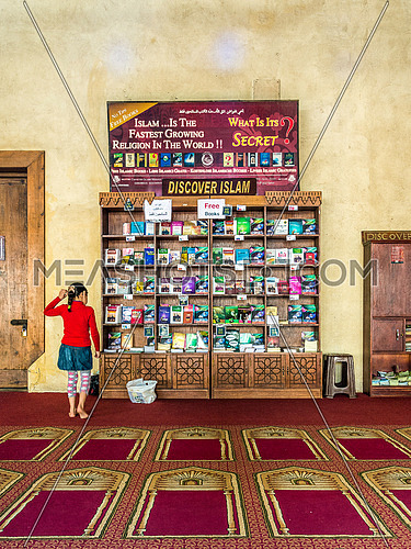 a girl standing looking towards the Discover Islam free book section for tourists