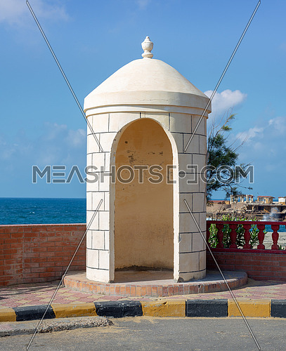 Old guard booth of white bricks with Mediterranean Sea, clear sky, and tree in the background located at Montaza public park, Alexandria, Egypt