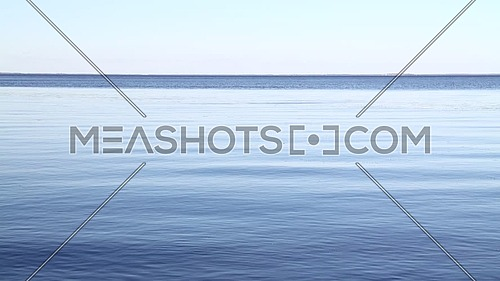 Waterscape of waves and ripples run in the wind on blue water surface of lake under clear blue sky, high angle view