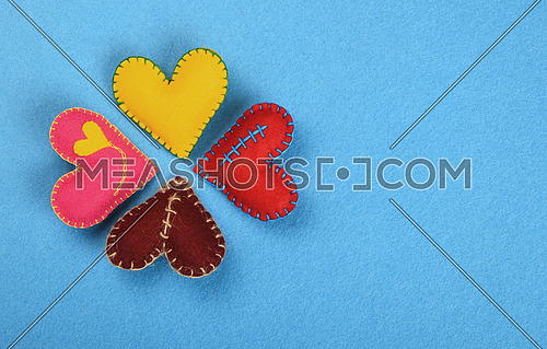 Felt craft and art, four colorful  handmade stitched toy hearts, red, pink, yellow and brown on blue background