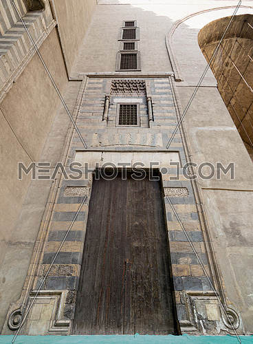 Wooden aged wall, wooden door and striped black and white marble decorations, Mosque of Sultan Hasan, Medieval Cairo, Egypt
