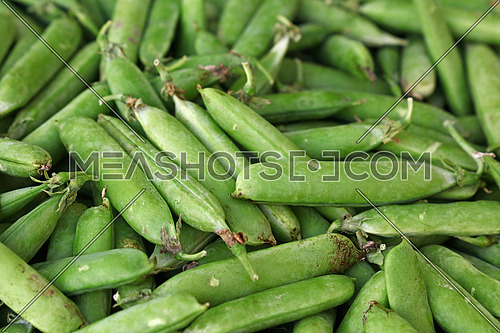 Close up fresh spring green peas pods on retail display of farmers market, high angle view
