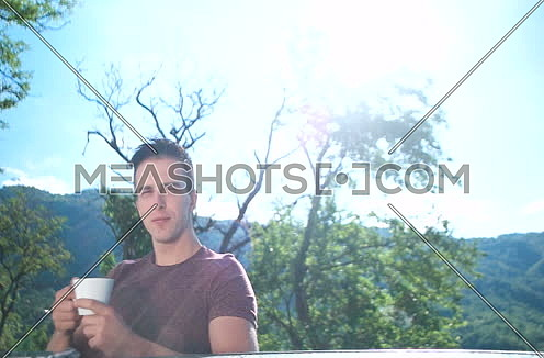 young couple having breakfast and drinking cooffee outside on huge balcony on sunny morning