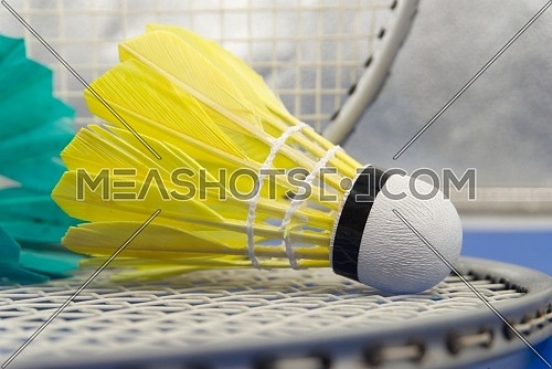 Badminton feather shuttlecocks in yellow with badminton rackets in a close up view