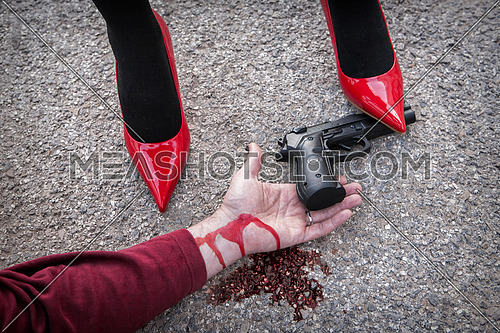 Man is dominated by a woman with red shoes, the shoe tread gun arm bloodied on the asphalt