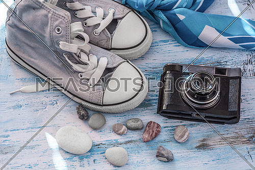 Travel still life with sneakers,camera and scarf on wooden board