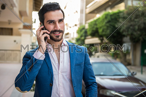 A young man is talking on a mobile phone in the street and he is happy