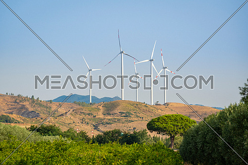 energy saving and green ecological concept with panorama view from wind turbine construction in field and meadow, Calabria Italy.