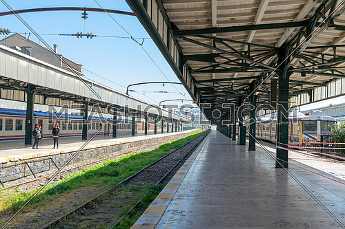 Istanbul, Turkey - April 26, 2017: Interior shot of abandoned Haydarpasha Railway Terminal with metal truss, stopped trains and two tourists visiting the place