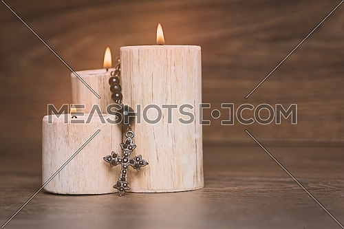 Black rosary on the Candle at wooden table,religion concept,vintage style.