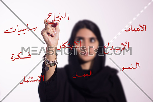 """Arabian middle eastern business woman writing with a marker on virtual screen in arabic different words """"sucess"""" isolated on white background"""