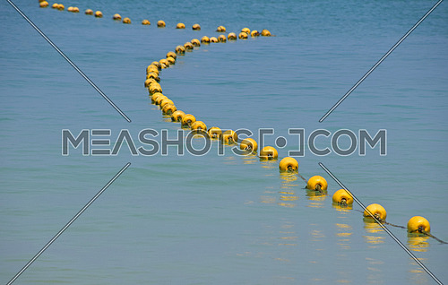 Chain of yellow polystyrene sea marker buoys with cable tow in blue sea water, in perspective