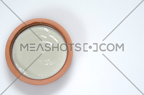 a rounded pottery plate filled with plane yogurt on a white background
