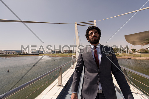 young middle eastern  businessman walking across modern bridge