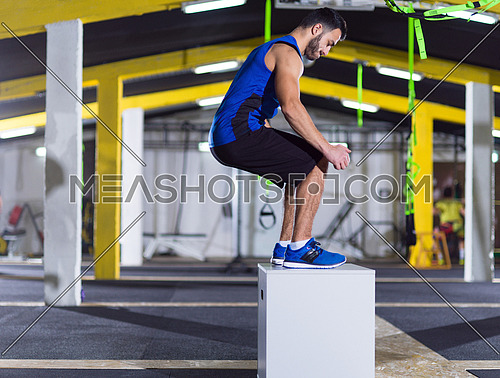 young athletic man training  jumping on fit box at crossfitness gym