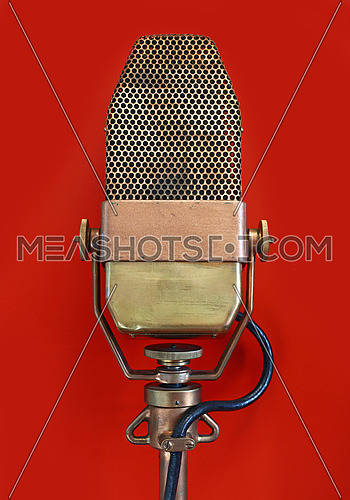 Vintage old retro vocal metal microphone side view close up over red background