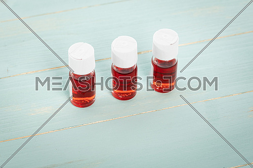 Three medicine vials filled with red liquid arranged in a row on green wooden