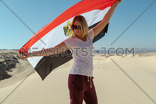Female tourists spreading Egyptian flag while exploring Sinai Trail from Ain Hodouda at day.