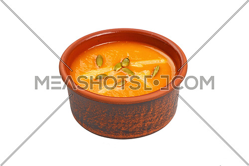 Ceramic bowl of pumpkin cream soup with seeds and cheese isolated on white background, high angle view