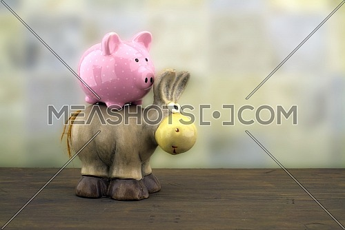 Cute little piggy bank and toy donkey close up side view against a blurred background