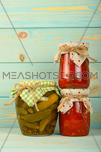 Two glass jars of homemade eggplant pepper salad and pickled cucumbers with green checkered textile decoration over blue painted wooden surface