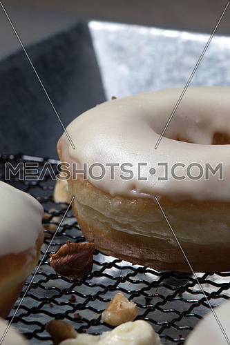 side view  of white glazed donuts with walnuts aside