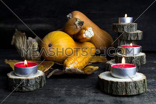 Happy Thanksgiving Day, Decoration on a wooden table with Pumpkins, Corncob, Burning Candles and autumn leaves