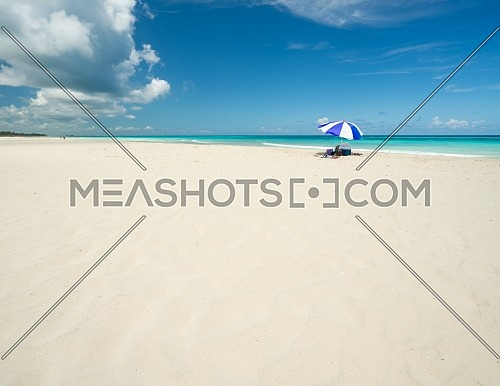 Wonderful beach of Varadero during a sunny day, fine white sand and turquoise and green Caribbean sea,on the right one blue parasol,Cuba.concept photo,copy space.