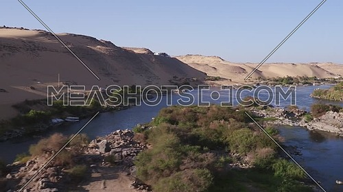 Drone shot Fly Over The River Nile at Aswan at day showing sailboeats, Mountain and plants.