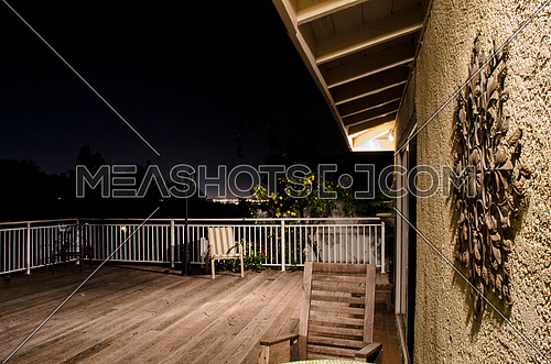 A balcony with wooden floor, chairs and tables, white fence and a lemon tree on the background