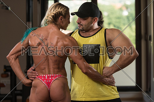 Portrait Of A Middle Aged Woman Posing Bodybuilding Poses In Modern Fitness Center With Her Partner