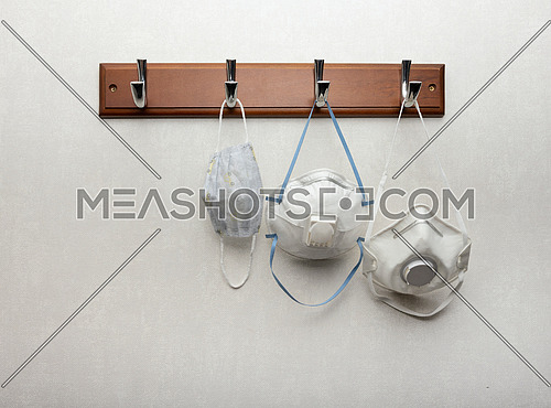 Close up several white disposable facepiece respirator masks with exhalation valves hanging on clothes rack as essential safety accessory during pandemic, low angle view