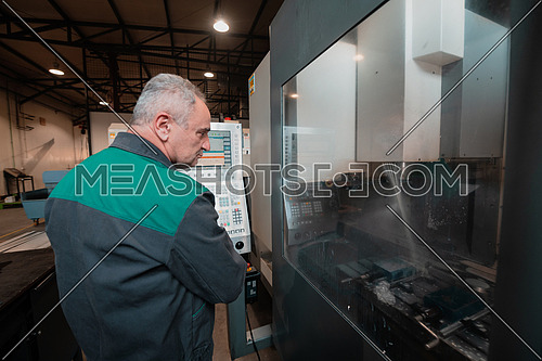 A smart factory worker or engineer makes machines in a production workshop. The concept of industry and engineering. High quality photo