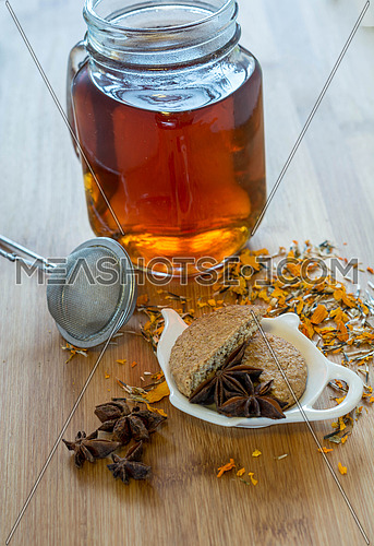 Tea,tea stainer, dried cinnamon, vegan cookies and anise on wood
