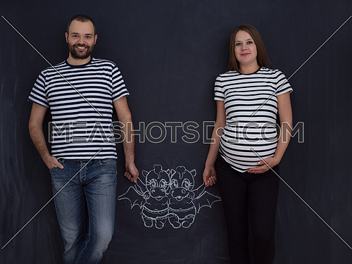Conceptual photo of pregnant couple drawing their imaginations about the future life with children on chalk board